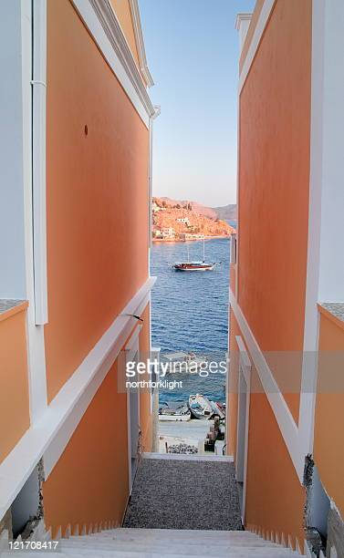 symi harbor view between two houses - symi stock photos and pictures