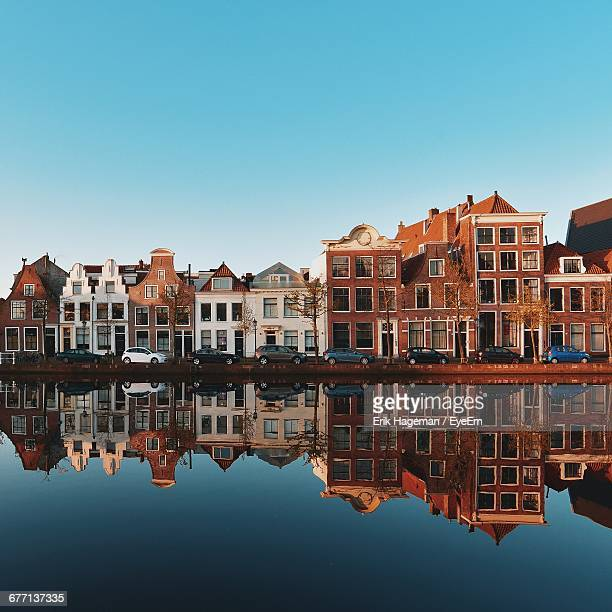 symmetric view of buildings reflecting in canal against clear blue sky - haarlem fotografías e imágenes de stock