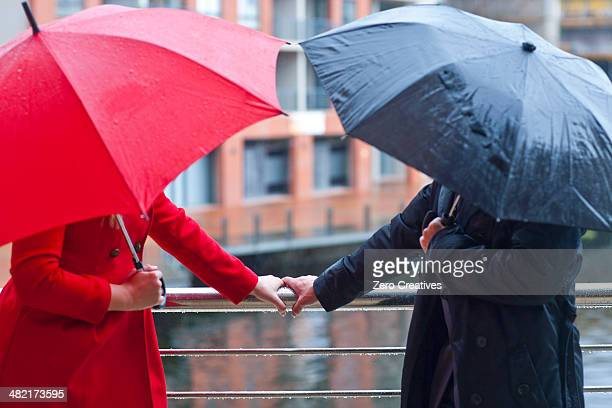 symmetrical couple holding handrail and carrying umbrella's - work romance stock pictures, royalty-free photos & images