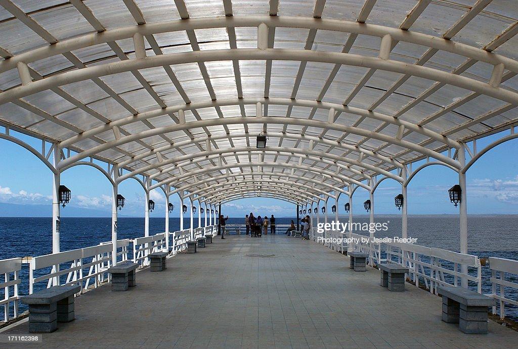 Symmetrical covered walkway by ocean : Stock-Foto