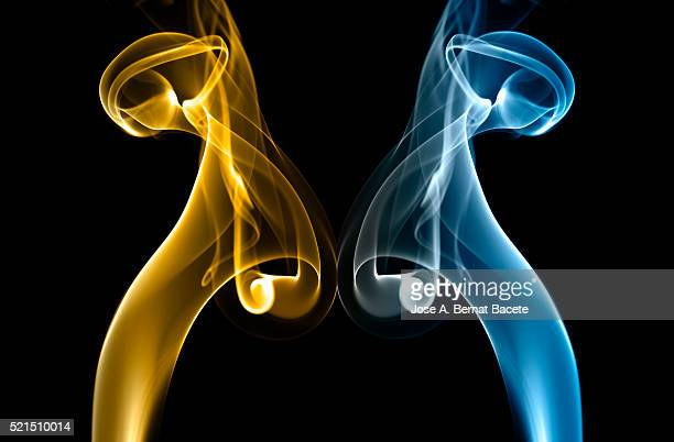 Symmetrical forms of smoke of blue and brown color on black bottom