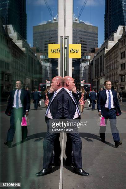 Symmetrical gentleman wearing a pinstripe suit talks on his phone, reflected in plate glass in the City of London, the capital's financial district...