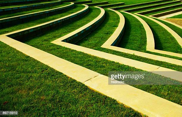 symmetrical green grass lawn with rows of steps at a park - amphitheatre stock photos and pictures