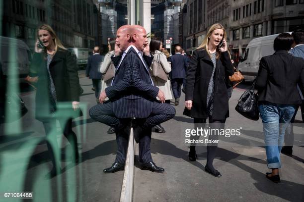 Symmetrical lady and a gentleman wearing a pinstripe suit talks on his phone, reflected in plate glass in the City of London, the capital's financial...