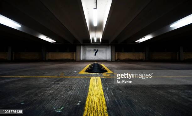 symmetrical parking garage with large number 7 on the wall - unterirdisch stock-fotos und bilder