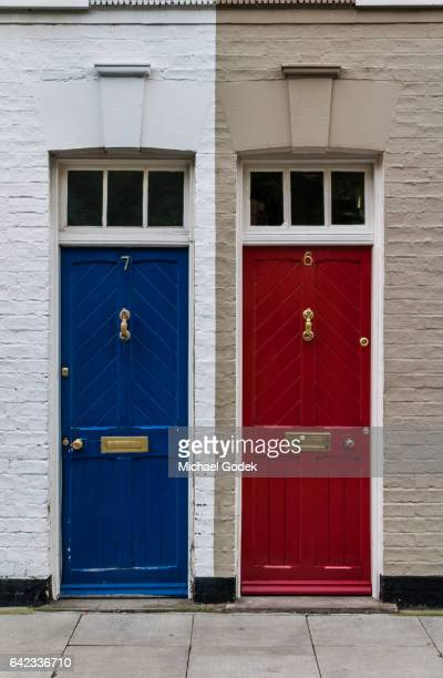 Symmetrical shot of a red and blue door side by side