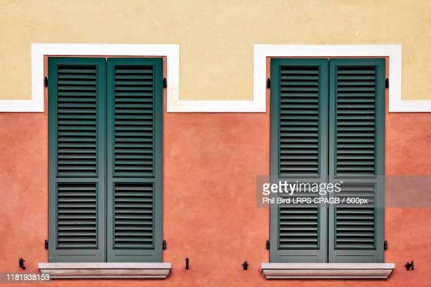 symmetrical shutters on a building in desenzano del garda - fensterladen stock-fotos und bilder