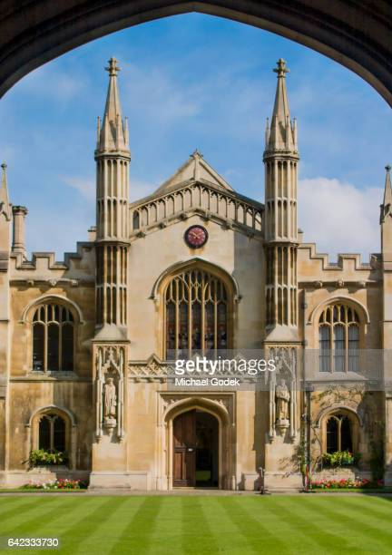 symmetrical view of lawn and cambridge university building framed by silhouetted archway - cambridge university stock pictures, royalty-free photos & images