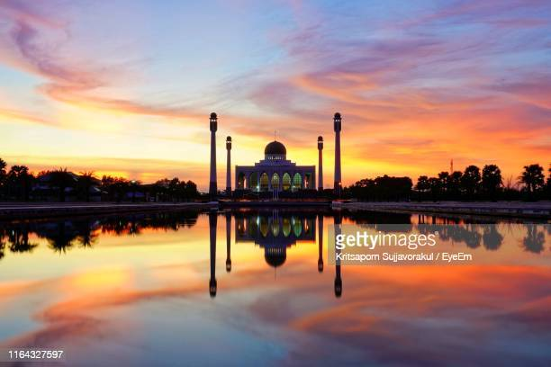 symmetry view of mosque by lake against dramatic sky during sunset - provincia di songkhla foto e immagini stock