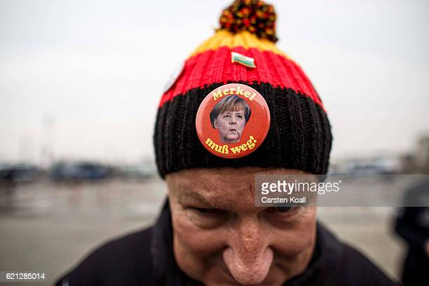A sympathiszer wears a cap in the colors black red yellow and a button with the conterfei of German Chancellor Angela Merkel as rightwing activists...