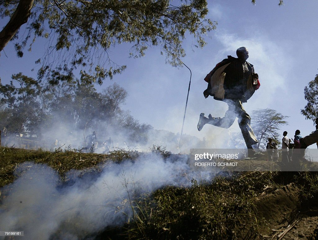A sympathizer of presidential candidate Raila Odinga runs through a cloud of tear gas during clashes with Kenyan police in a road leading outside the Kibera slum in Narobi, Kenya, 03 January 2008. Kenyan police used tear gas, live rounds and water cannon Thursday to disperse protestors marching on Nairobi city centre to attend a banned rally organised by defeated presidential challenger Raila Odinga. Odinga had called for one million supporters to gather in a Nairobi park to protest the result of last week's election in which President Mwai Kibaki was re-elected amid widespread allegations of vote-rigging. AFP PHOTO/Roberto SCHMIDT