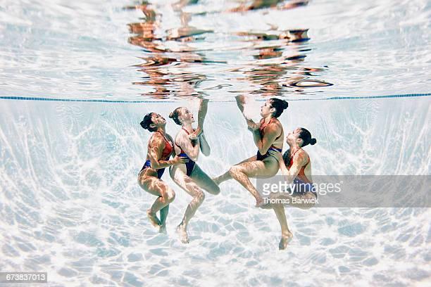 Synchronized swim team performing lift