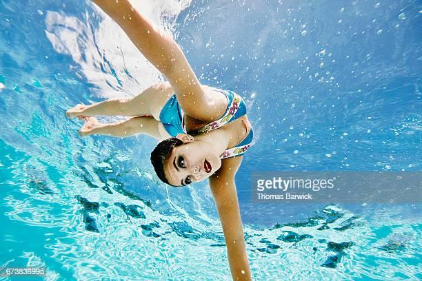 Synchronized swimmer diving underwater