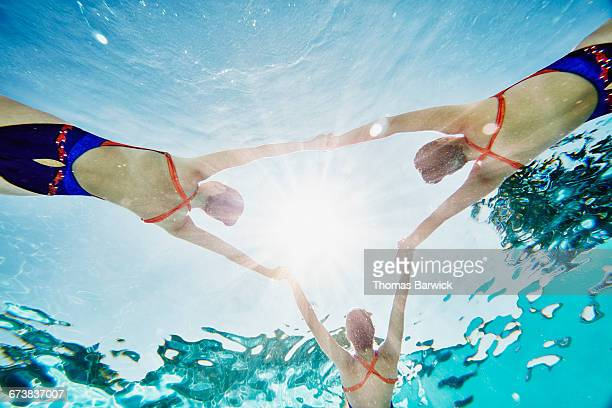 Synchronized swimmers holding hands while floating