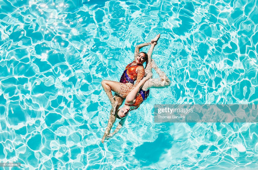 Synchronized swimmers performing routine : Stock Photo