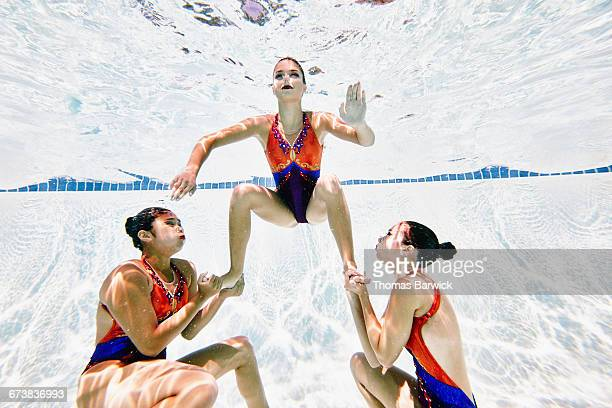 Synchronized swimmers preparing to lift teammate