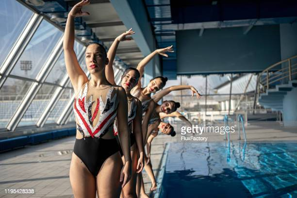 synchronized swimming team on the side of the pool - team sport stock pictures, royalty-free photos & images