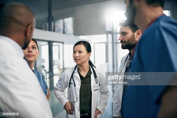 synchronizing their tasks before shift - group of doctors stock pictures, royalty-free photos & images
