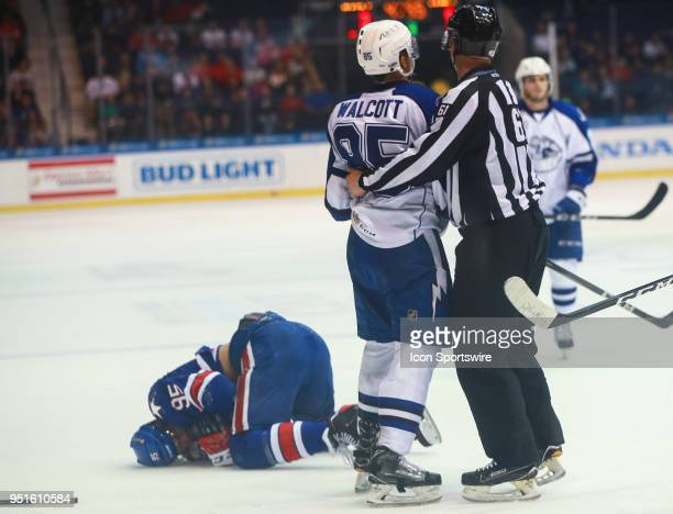 Syracuse Crunch defenseman Daniel Walcott is held by the linesman after hitting Rochester Americans right wing Justin Bailey who lays on the on the...