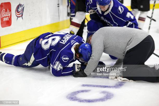 Syracuse Crunch forward Otto Somppi is examined by a trainer after taking a hard hit into the boards during the second period of the American Hockey...