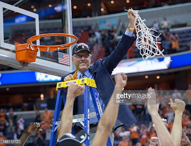 Syracuse head coach Jim Boeheim holds up the net to players after Syracuse defeated Marquette 5539 in the NCAA Tournament East Regional final at the...