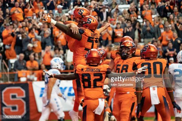 Syracuse Orange Offensive Lineman Aaron Roberts leaps in the air with Syracuse Orange Quarterback Eric Dungey celebrating a touchdown during the...
