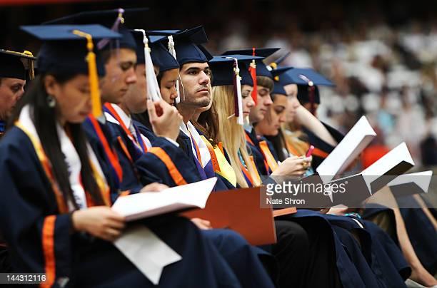 Syracuse University graduates sit and read programs during the 2012 Syracuse University Commencement at Syracuse University on May 13, 2012 at the...