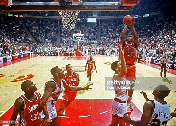 Syracuse's Billy Owens takes a jump shot over the University of Connecticut defense Hartford Connecticut 1990