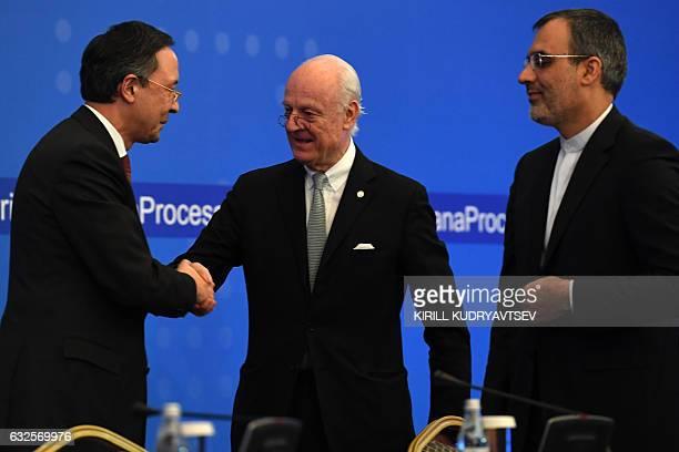 UN Syria envoy Staffan de Mistura shakes hands with Kazakh Foreign Minister Kairat Abdrakhmanov as Iran's Deputy Foreign Minister Hossein Jaber...