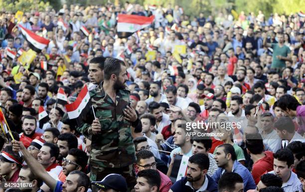 Syria football fans react as they watch the FIFA World Cup 2018 qualification football match between Iran and Syria on a large screen at the AlJalaa...