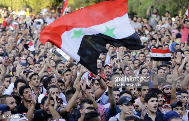 Syria football fans watch the FIFA World Cup 2018 qualification football match between Iran and Syria on a large screen at the AlJalaa stadium in...