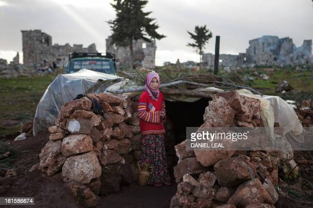 A Syria girl stands at the entrance of a makeshift home set up in the catacombs of the ruins of an ancient building in the ancient Roman city of of...