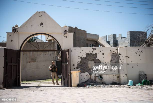 Syriac Christian militiaman stands next to a heavily damaged church wall in Saint John's Church during an easter ceremony in the nearly deserted...