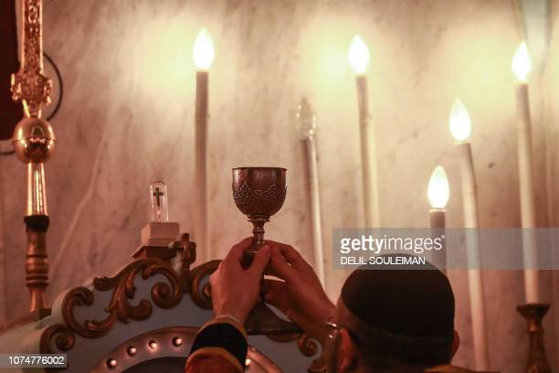 Syriac Orthodox priest holds up the chalice as he leads Christmas morning mass at the Syriac Orthodox Church of the Virgin Mary in Qamishli in...