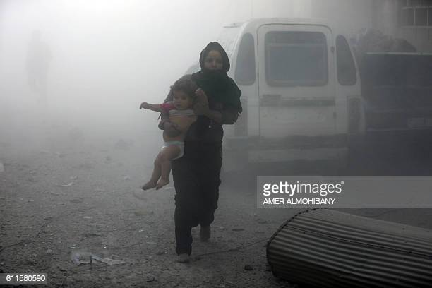 A Syrian 2oman carrying a child emerges from a dust cloud following a reported airstrike on Kafr Batna in the rebelheld Eastern Ghouta area on the...
