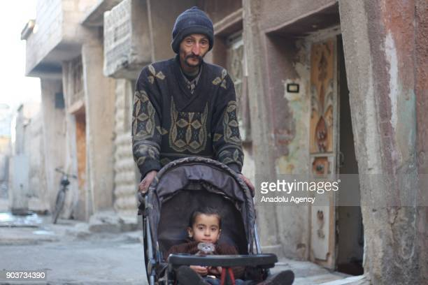 Syrian Abu Qasim who lost his job due to health issues after Assad Regime's blockage on Easthern Ghouta pushes his baby with a pushchair in Easthern...