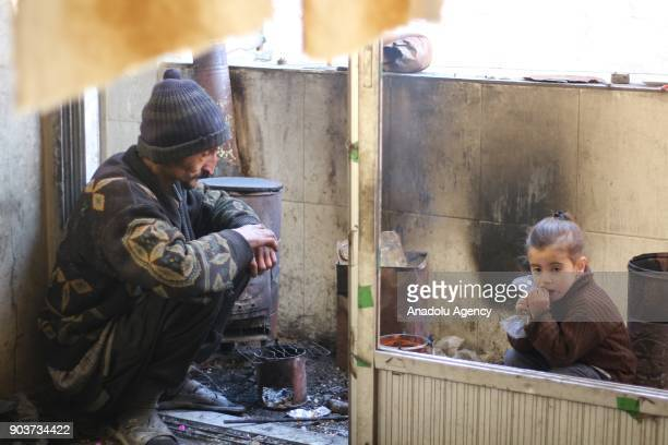 Syrian Abu Qasim who lost his job due to health issues after Assad Regime's blockage on Easthern Ghouta sits on the floor as he looks after his...