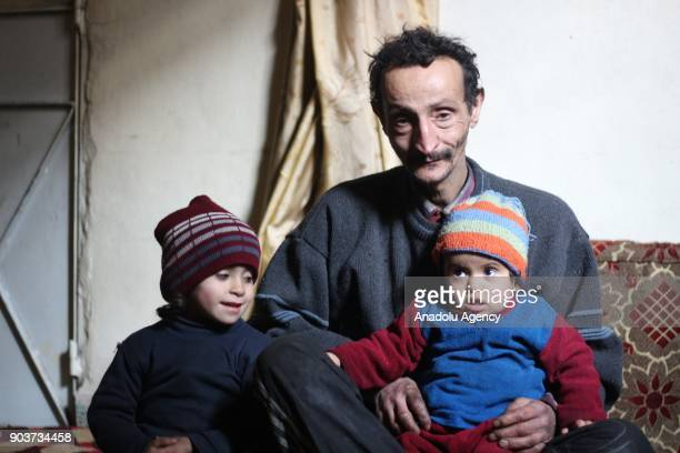 Syrian Abu Qasim who lost his job due to health issues after Assad Regime's blockage on Easthern Ghouta poses for a photo with his children in...