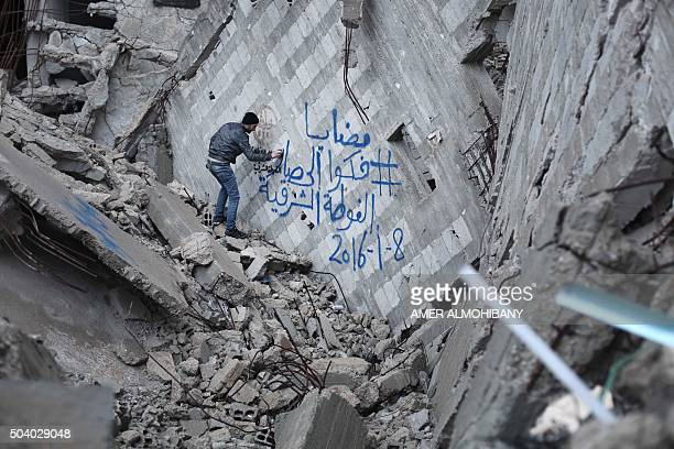 A Syrian activist sprays graffiti in solidarity with the besieged town of Madaya on a wall of a damaged building in the Kafr Batna town in the...