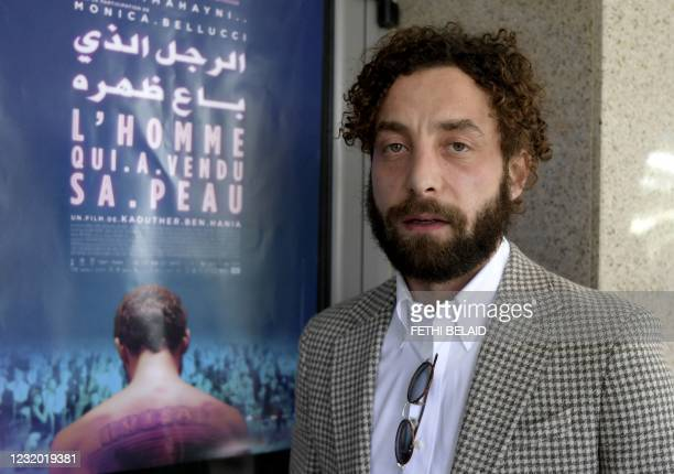 """Syrian actor Yahya Mahayni poses for a picture in front of the poster of the Tunisian film """"The man who sold his skin"""" in which he stars, during its..."""