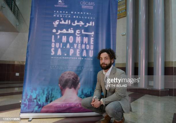 """Syrian Actor Yahya Mahayni poses for a picture in front of the poster of """"The man who sold his skin"""" during its first screening in the country, in..."""