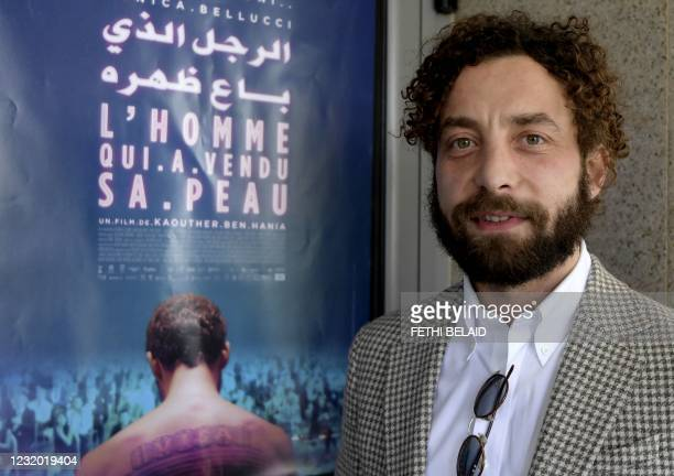 """Syrian Actor Yahya Mahayni poses next to the poster of """"The man who sold his skin"""" upon his arrival to attend its first screening in the country, in..."""
