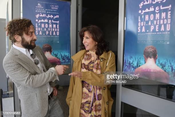"""Syrian actor Yahya Mahayni poses with Tunisian director and screenwriter Kaouther Ben Henia in front of the poster of the Tunisian film """"The man who..."""
