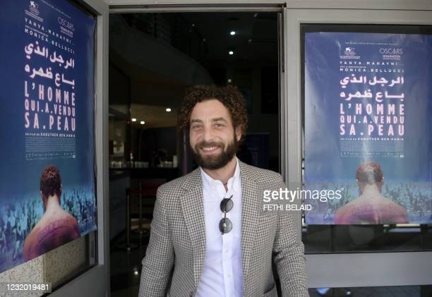 """Syrian Actor Yahya Mahayni walks past the poster of """"The man who sold his skin"""" upon his arrival to attend its first screening in the country, in the..."""