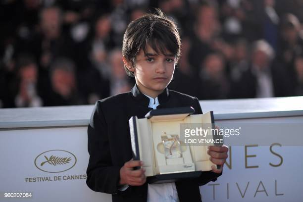 Syrian actor Zain alRafeea poses with the trophy on May 19 2018 during a photocall after Lebanese director and actress Nadine Labaki won the Jury...