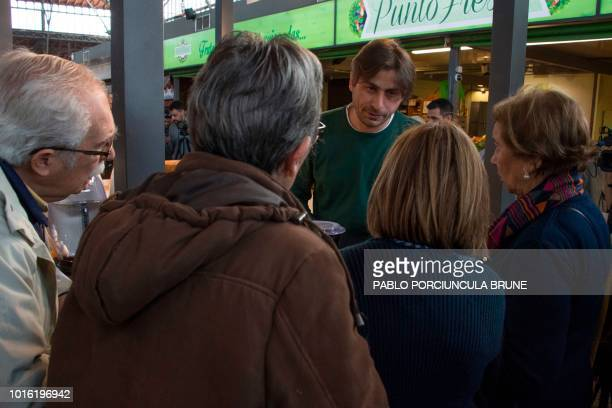 Syrian Ahmed Adnan Ahjam a former Guantanamo inmate speaks with customers during the opening of his Arab gastronomy shop at the Mercado Agricola in...