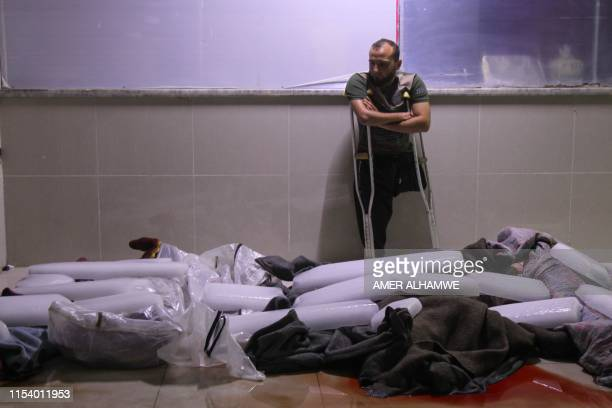 A Syrian amputee looks at bodies of civilians reportedly killed in regime airstrikes on the town of Muhambal in the northern Idlib province on July 6...