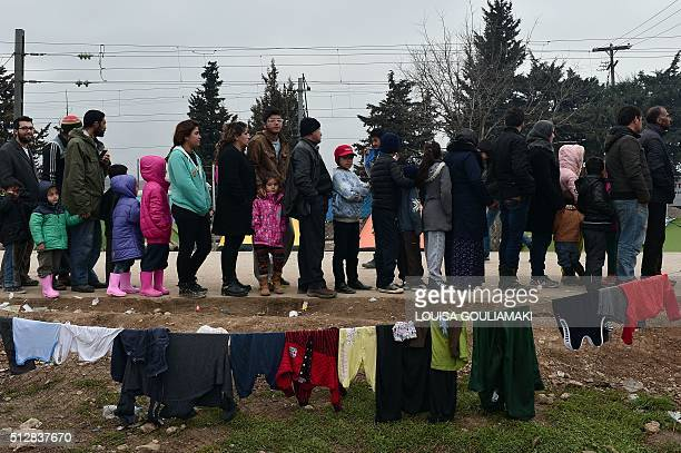 Syrian and Iraqi refugees trapped at the GreekMacedonian border queue for food at a makeshift camp in Idomeni on February 28 2016 Greece warned the...