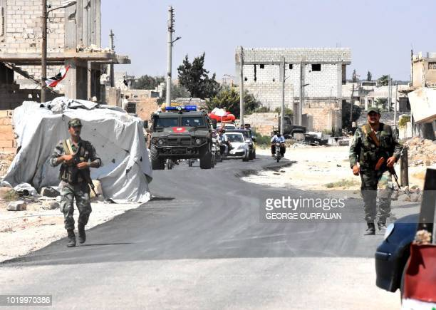 Syrian and Russian forces stand guard as civilians enter the Abu Duhur crossing on the eastern edge of Idlib province on August 20 2018 Civilians are...