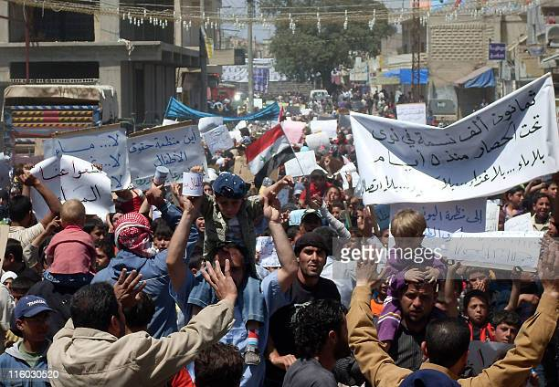 S Syrian antigovernment protesters hold banners calling for an end to a military siege in Nawa near the southern town of Daraa the epicentre of...
